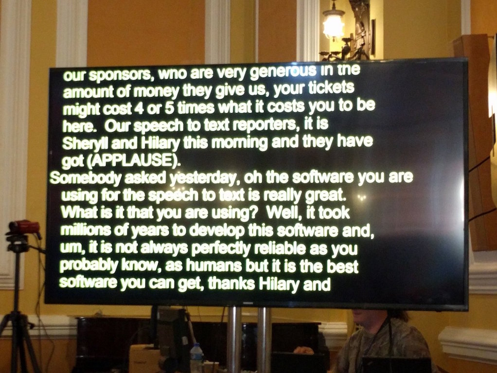 A television screen with yellow text on a black background, showing a transcript of somebody speaking.