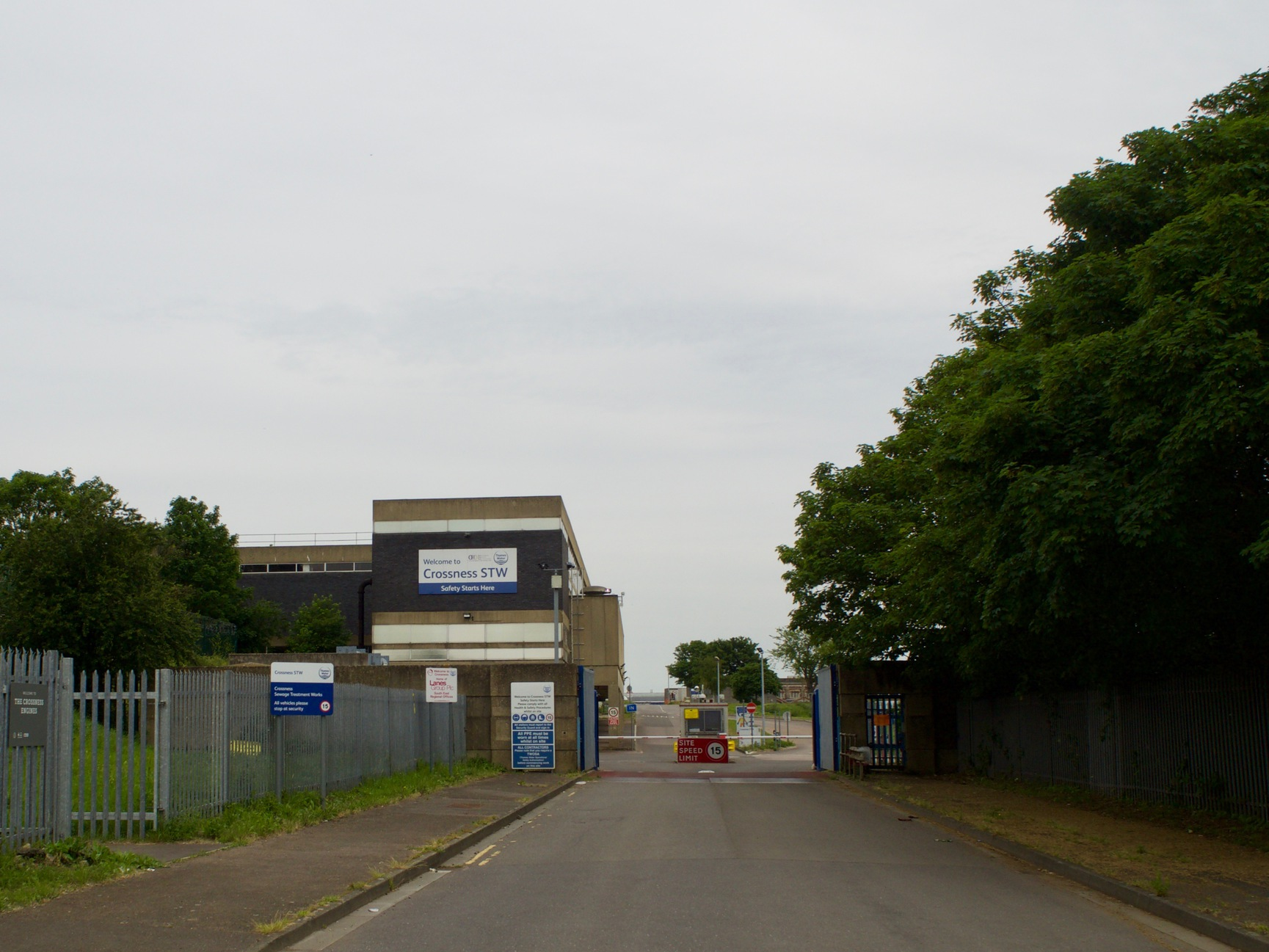 "A square building labelled ""Crossness STW"", with fences and a road barrier."
