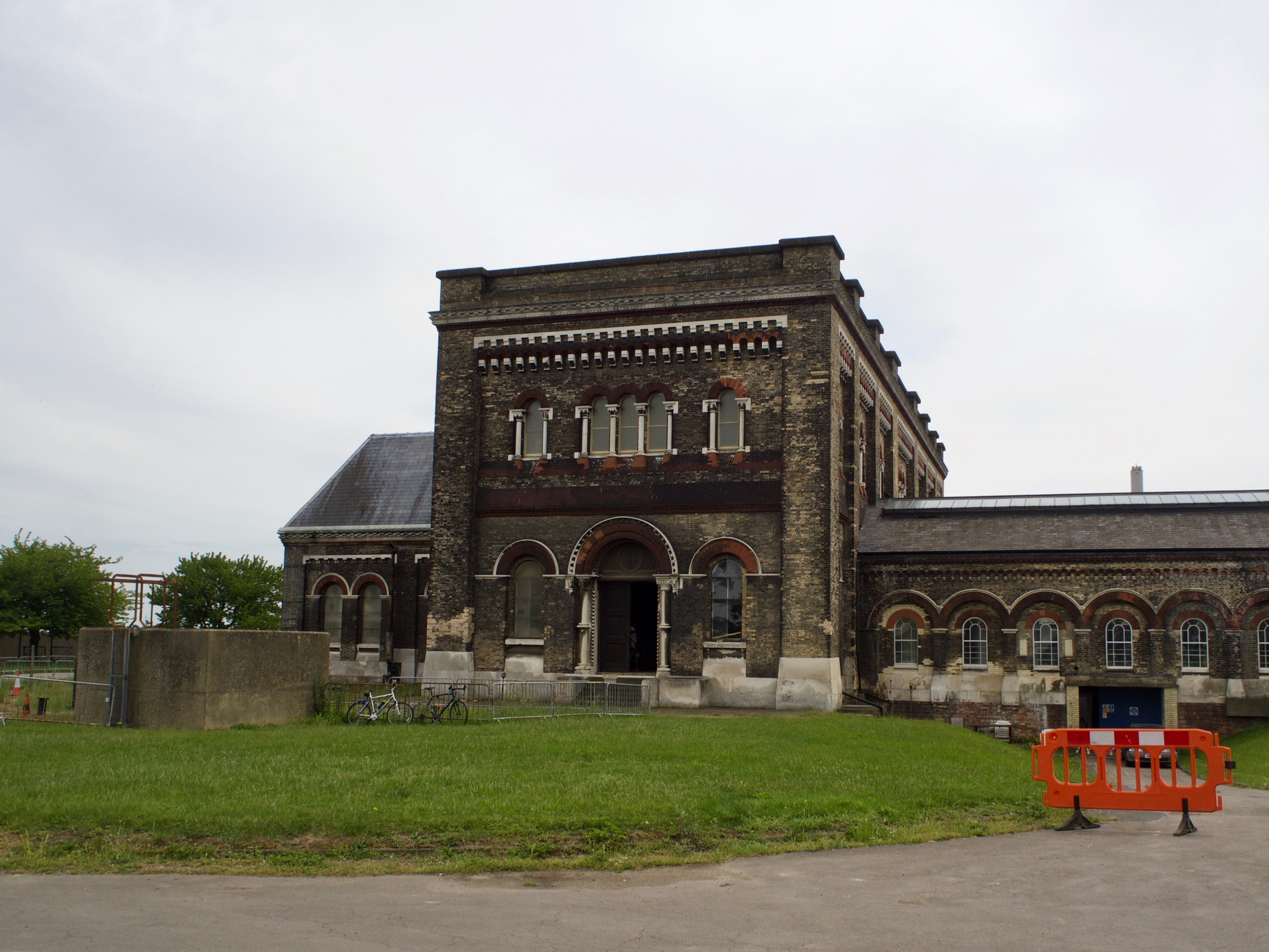 A dark brown building with rounded arches along the doors and windows, an orange safety barrier and a few bicycles.