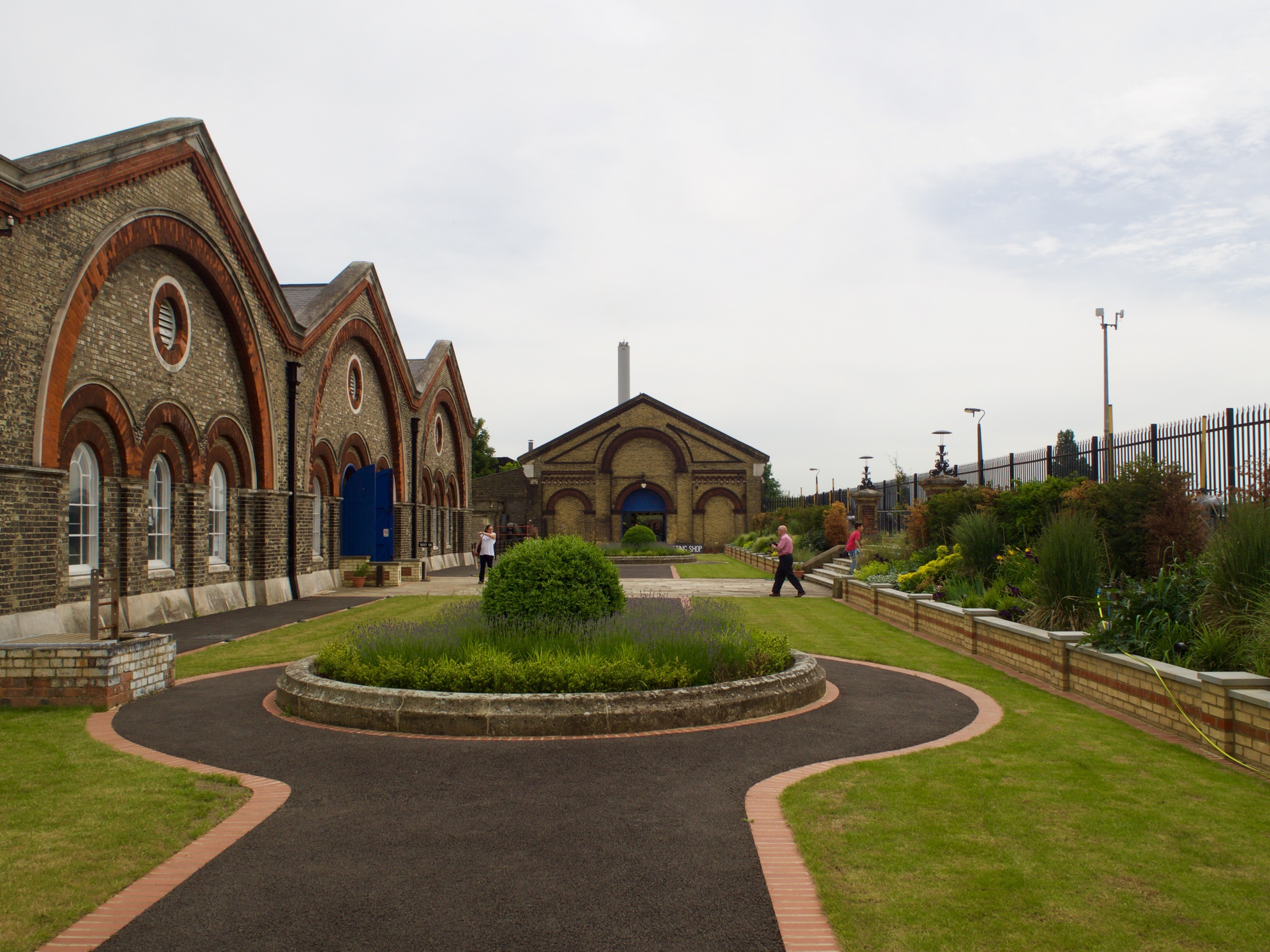 Looking onto a courtyard area with three buildings to the left, some grassy patches and another arched building in the distance.