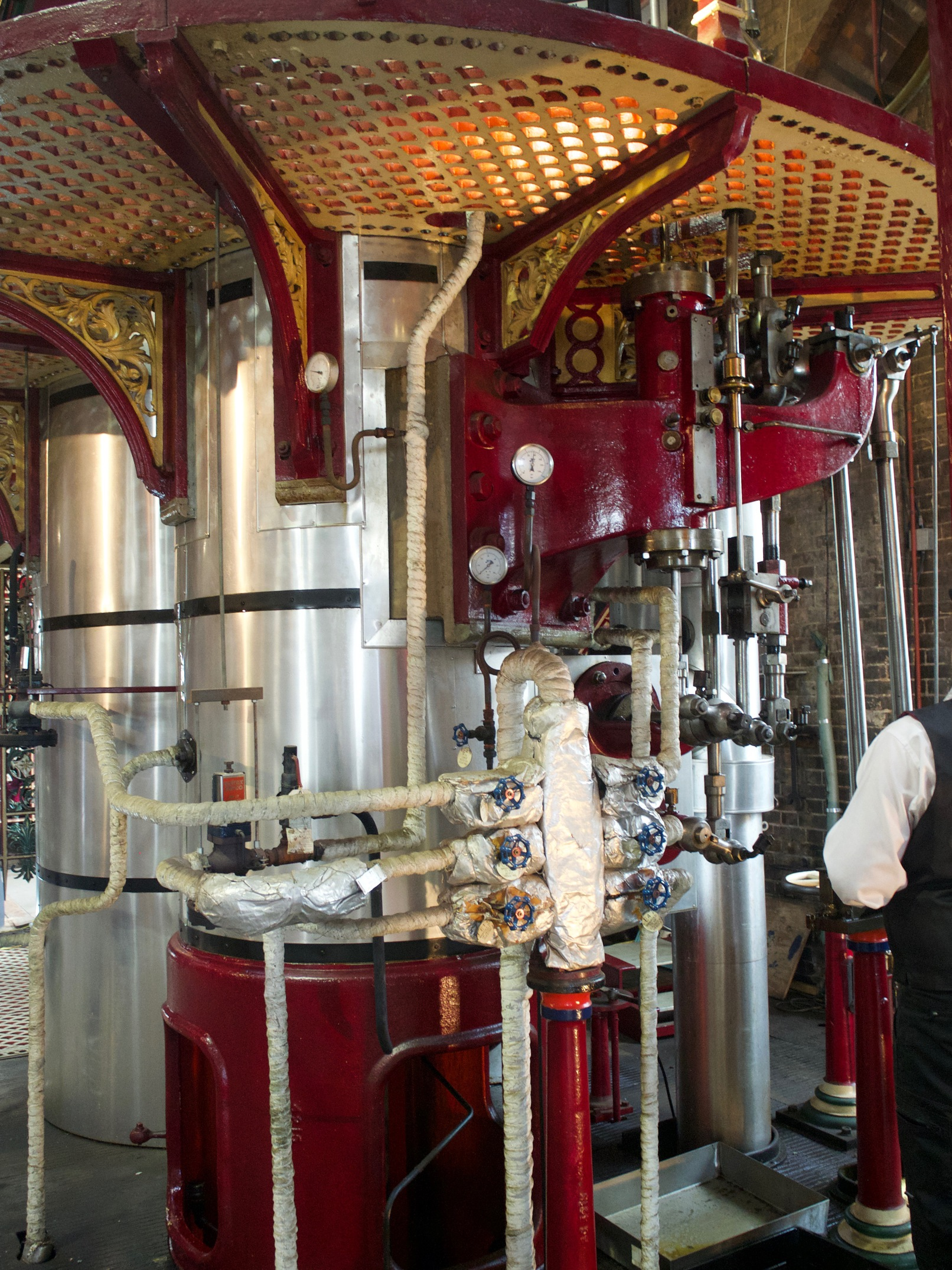 A series of pipes and tubes surrounding cylindrical boilers. Some of the metalwork has red and gold decorations.
