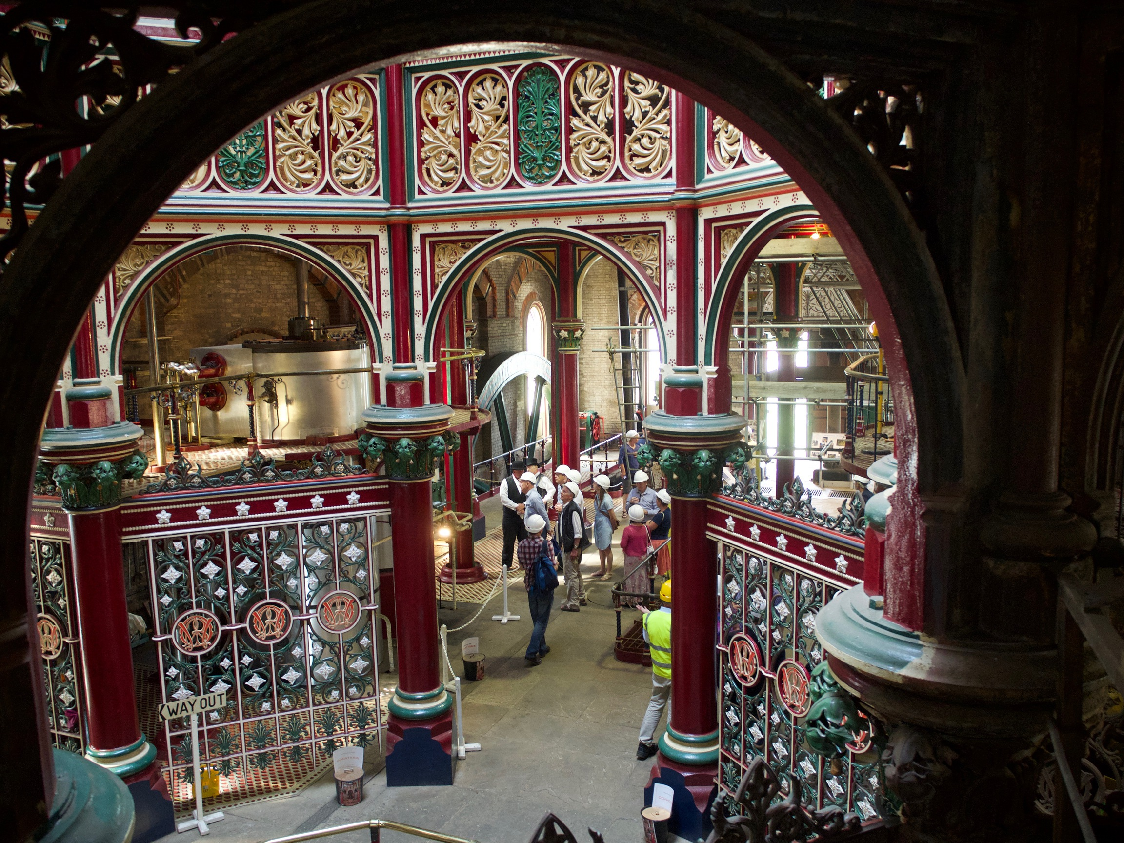 Looking down on gold, red and green metalwork adorning the top of an octagonal area. Red columns mark the octagon.