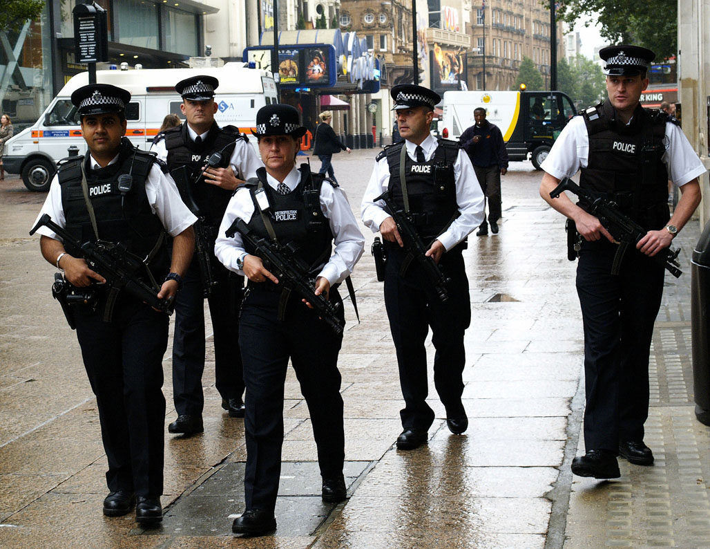 Five police officers walking down a street, all holding large guns which are pointed towards the ground.