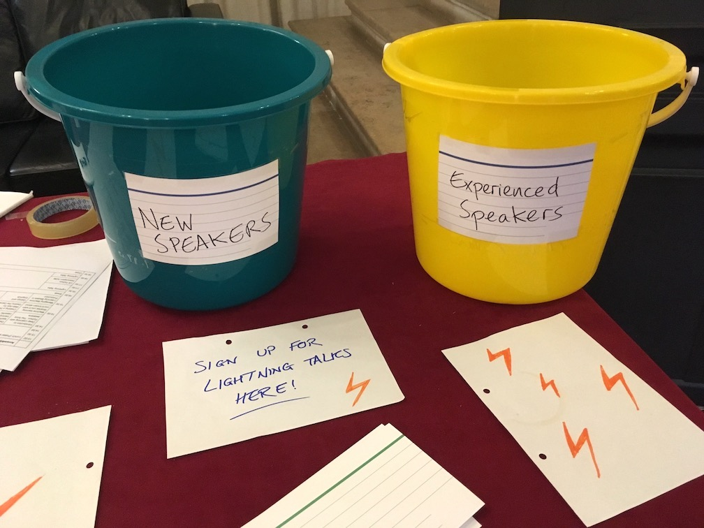 "Two buckets: one green (left), labelled ""New speakers"", another yellow (right), labelled ""Experienced speakers"". Below the buckets is a handwritten label ""Sign up for lightning talks here""."