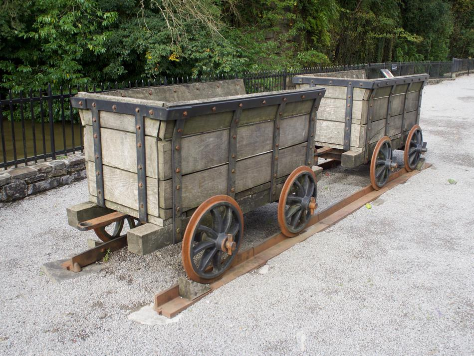 A pair of wooden carts on rusted railway tracks.