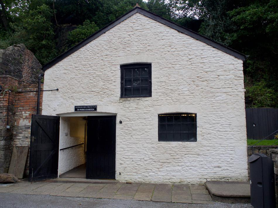 "A white building with two windows, black doors, and a small sign reading ""Tin Works exhibition""."