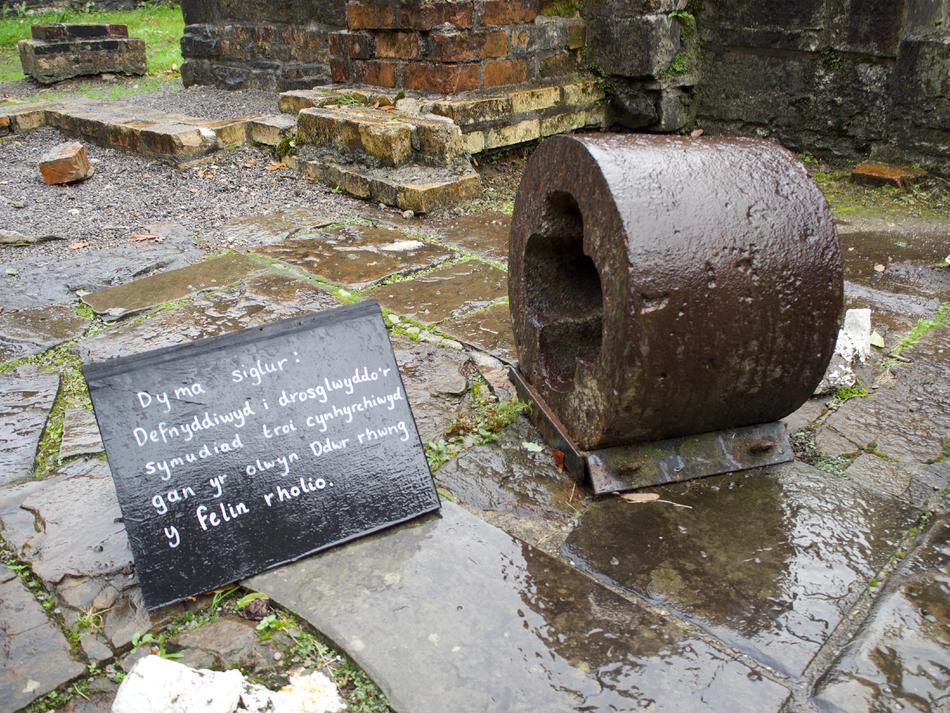 A small, rusted circular bearing next to a black sign with handwritten Welsh text.
