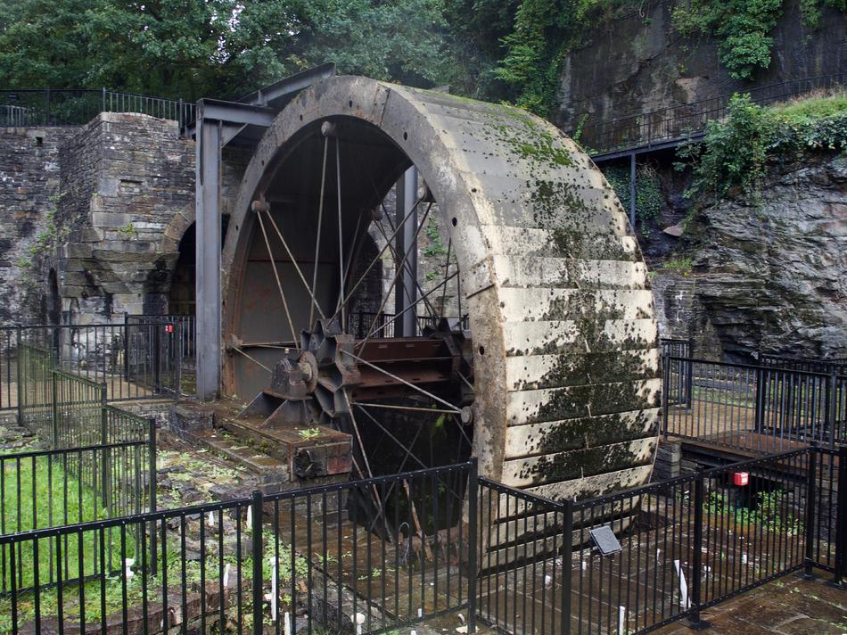 A metal waterwheel surrounded by black safety barriers.