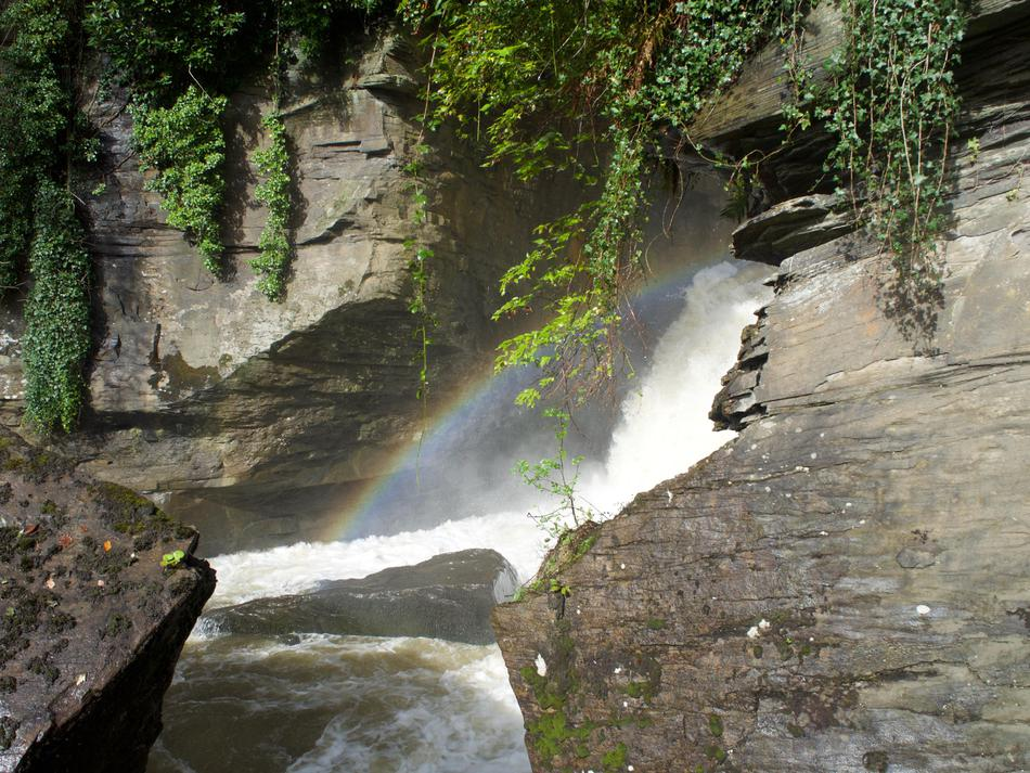 White spray among rocks in the waterfall, with a rainbow between the rocks.