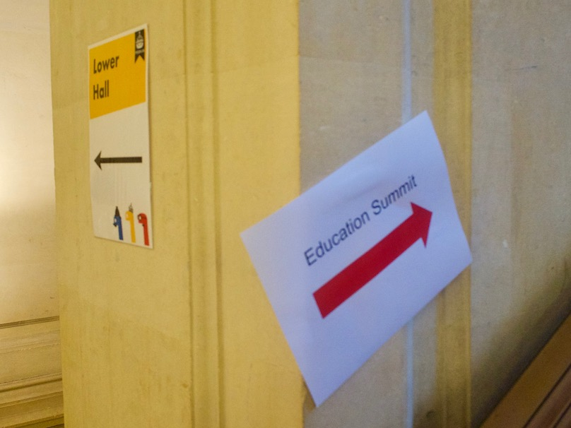 "A pillar with a white-and-yellow sign labelled ""Lower Hall"" on one side, and a sign with a red arrow labelled ""Education Summit"" on the right."