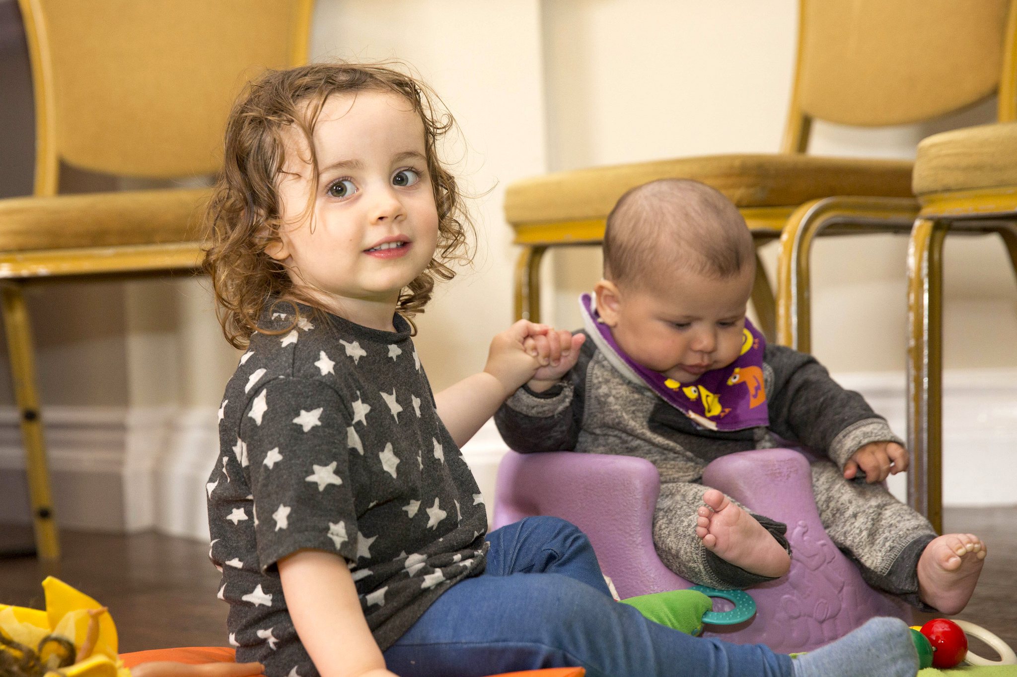 Two babies sitting on the floor with some chairs and toys.