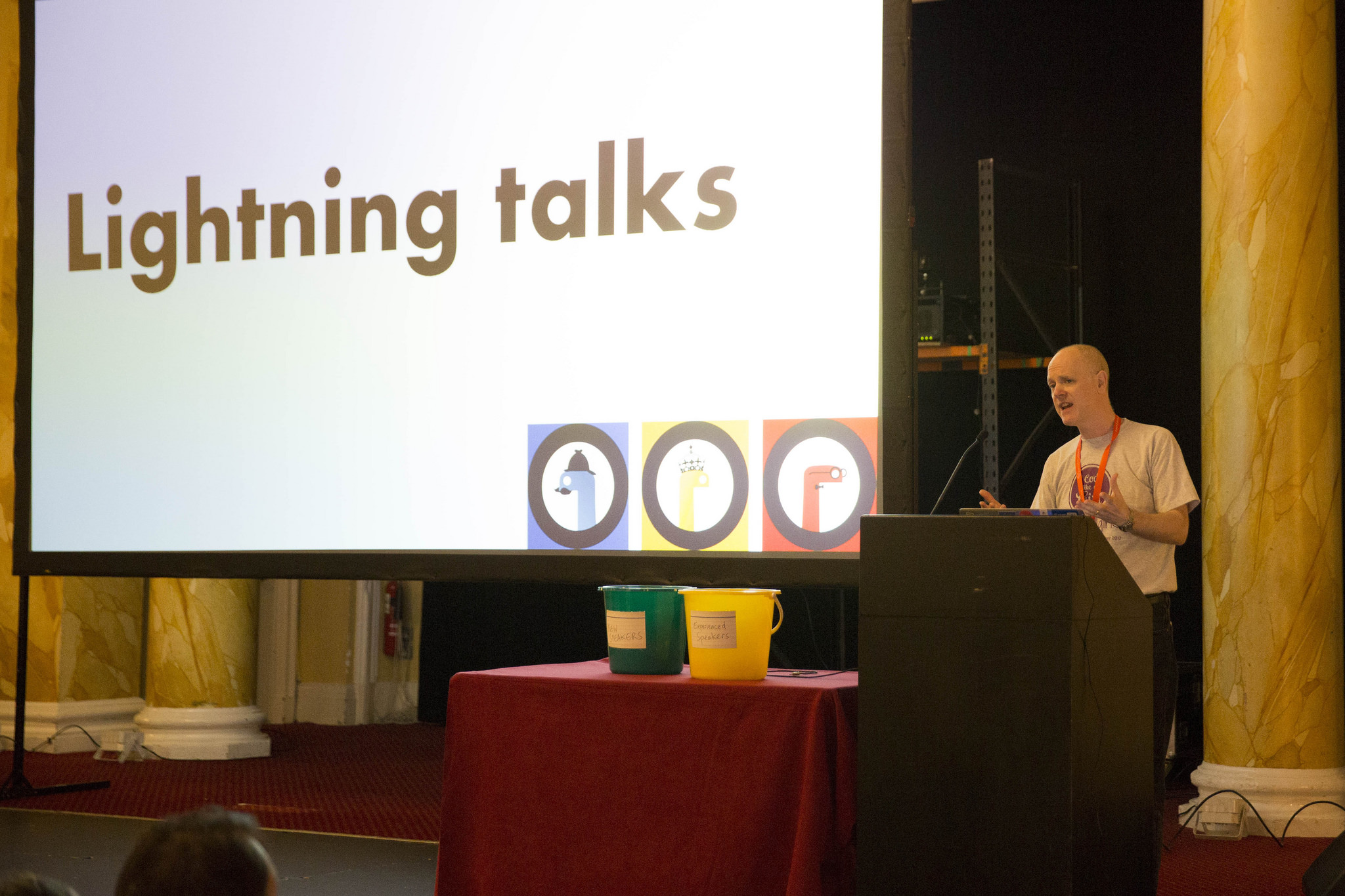 "A person at a lectern with a slide behind them saying ""Lightning talks"" and two buckets on the table."