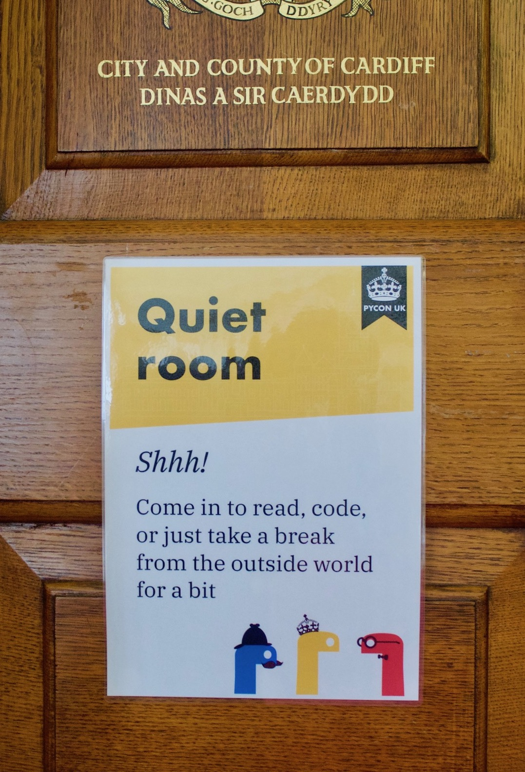 "A sign on a brown wood-panelled door, with a yellow stripe at the top labelled ""Quiet room""."