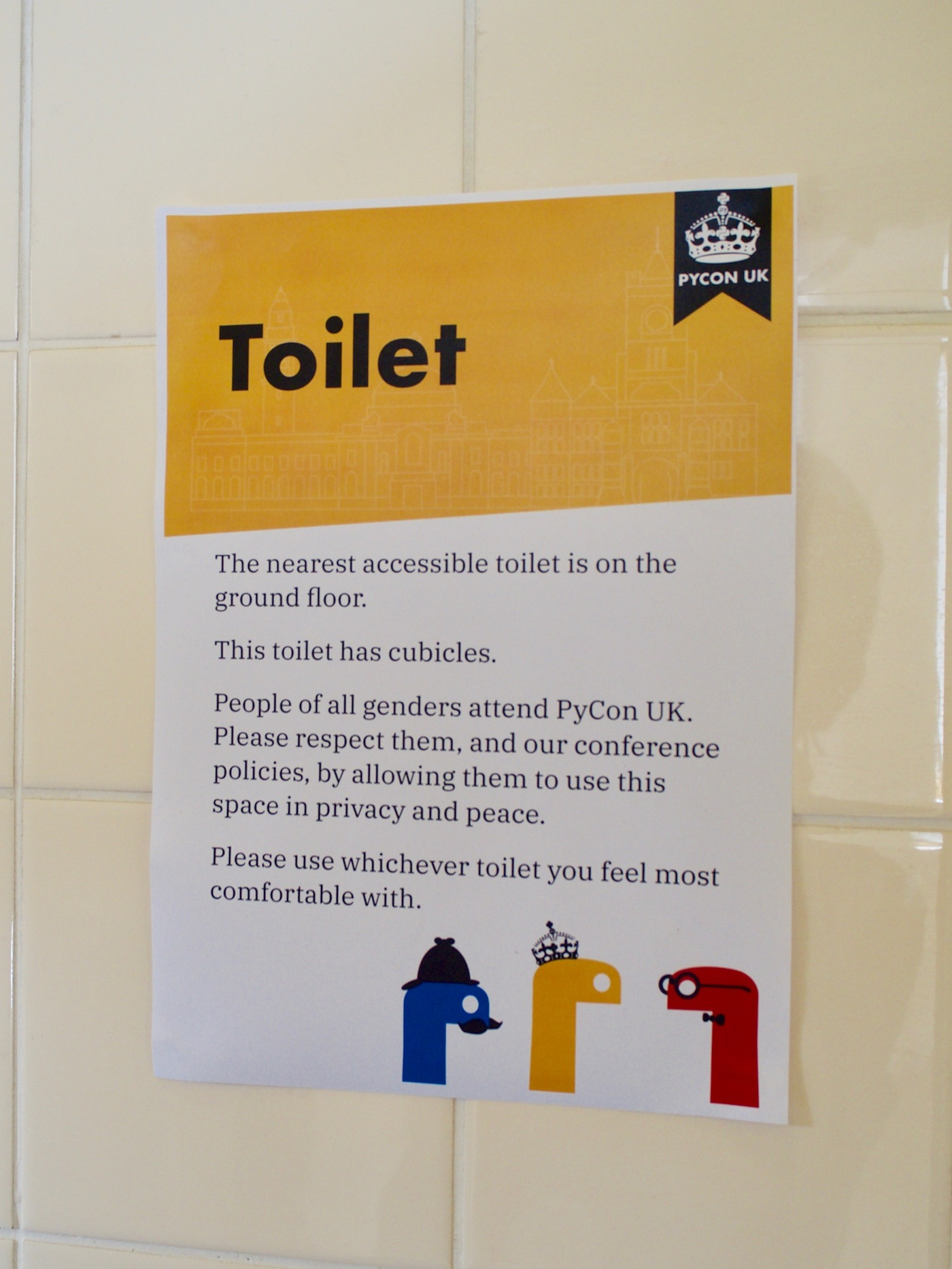 "A sign on bathroom tiling with a yellow stripe at the top labelled ""Toilet""."