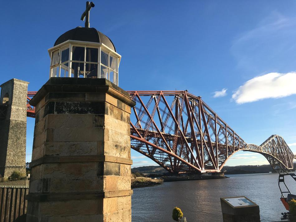 The lighthouse in the foreground on the left, with the bridge set against a blue sky in the background.