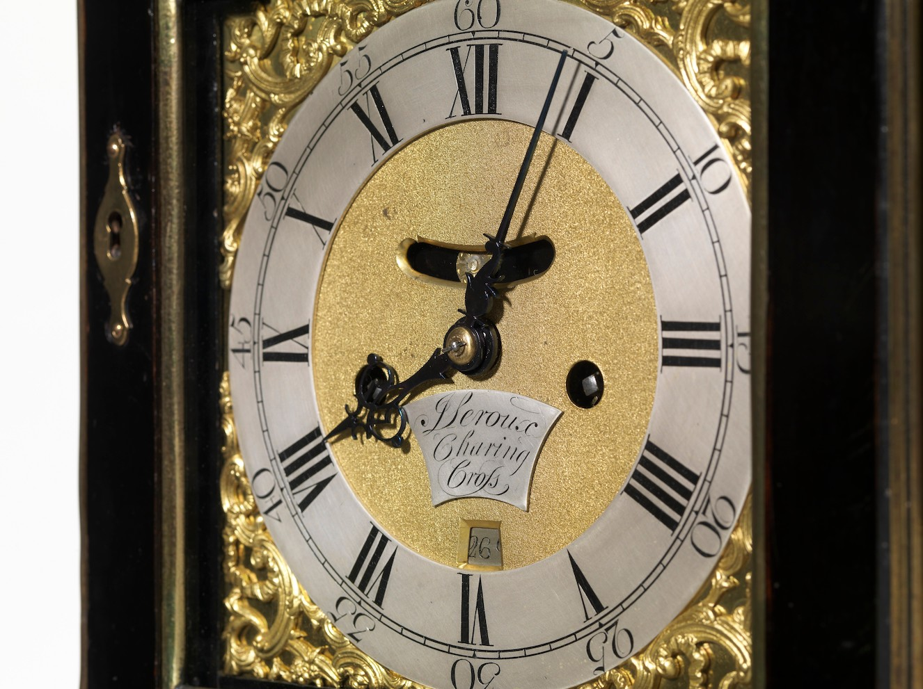 A clock face with Roman numerals and gold decoration.