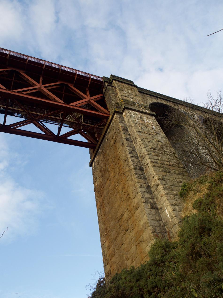 A yellowish-coloured stone viaduct, with the red girders of the bridge atop it.