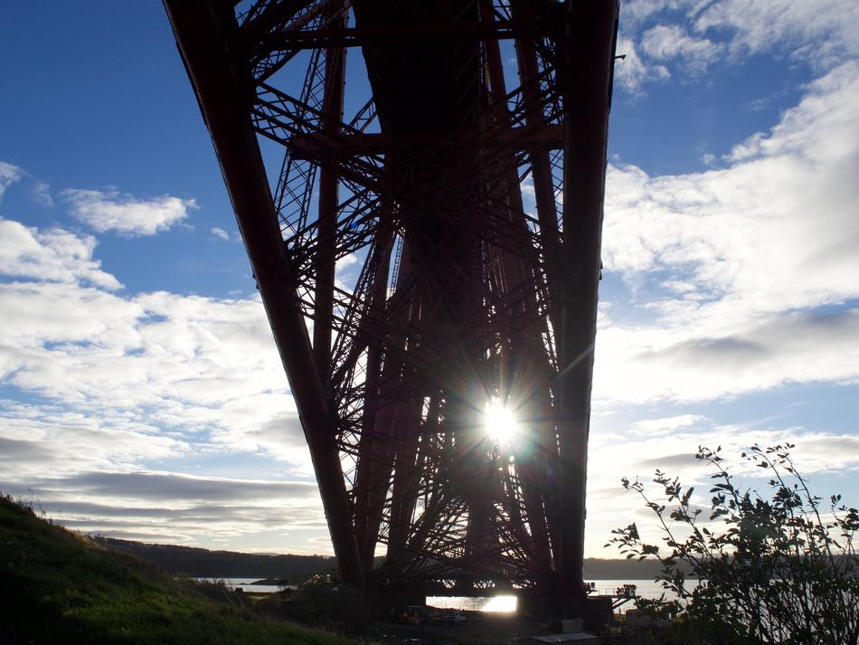 A silhouette of the girders in the bridge, looking up from underneath.