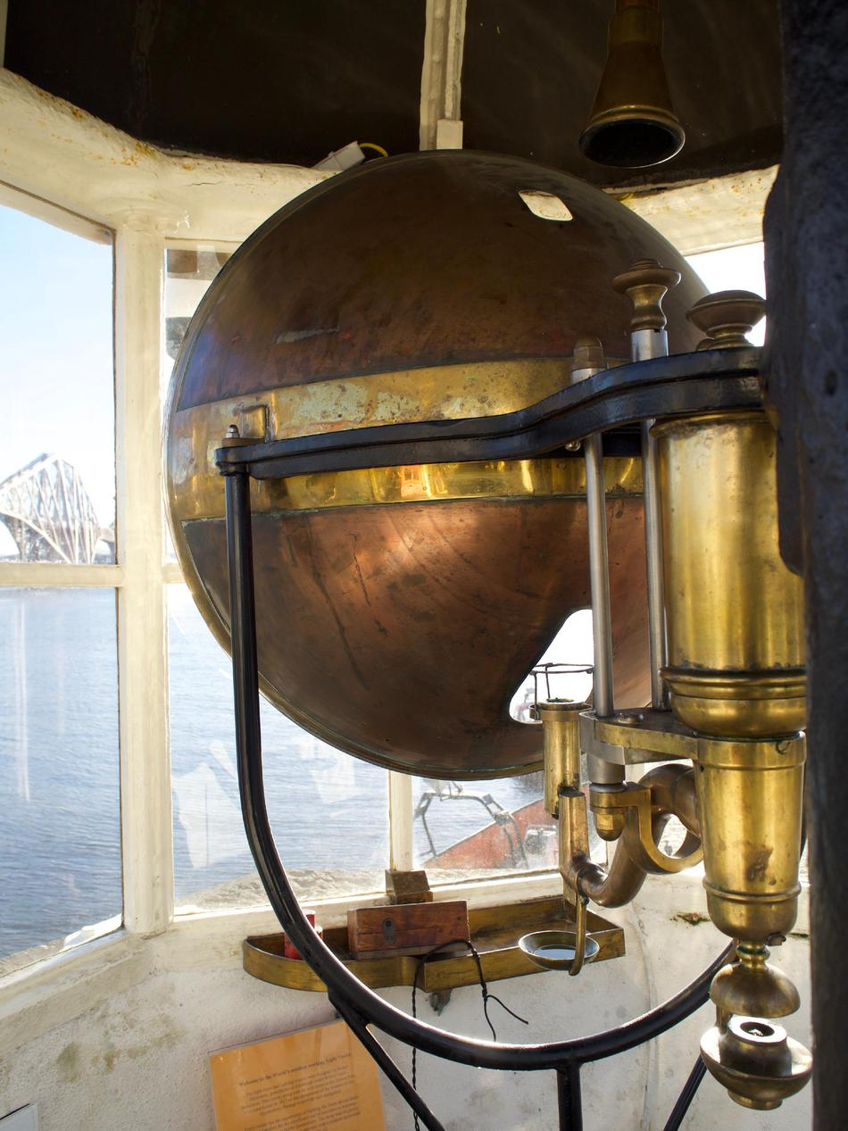 The back of a copper-coloured, parabolic lens looking out through a lighthouse window.