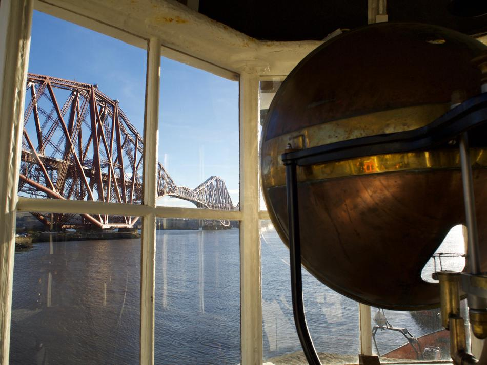 Looking from inside the lighthouse window, with a red bridge visible outside and part of a copper-coloured lamp housing inside.