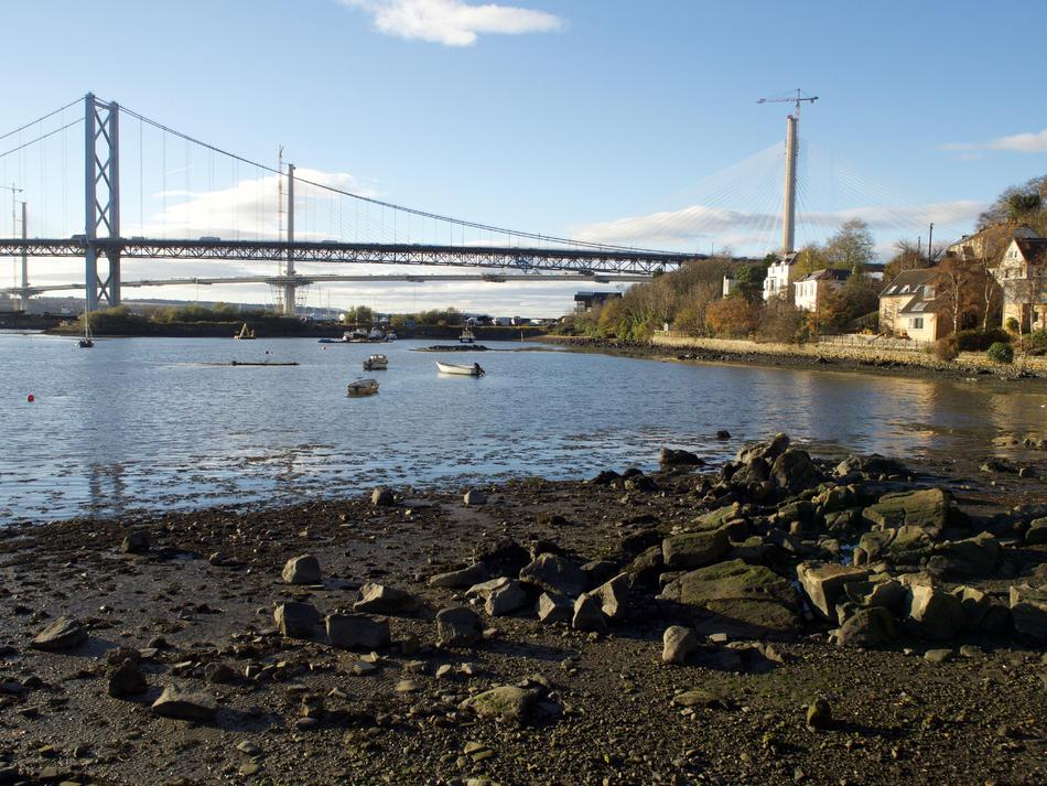 Photo from the water's edge, with two bridges in the background and a couple of boats in the water.