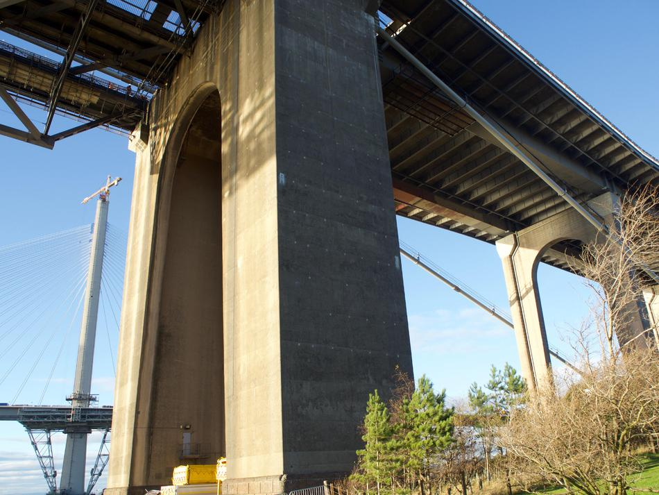 A single concrete support, with the ridged underside of the bridge visible.