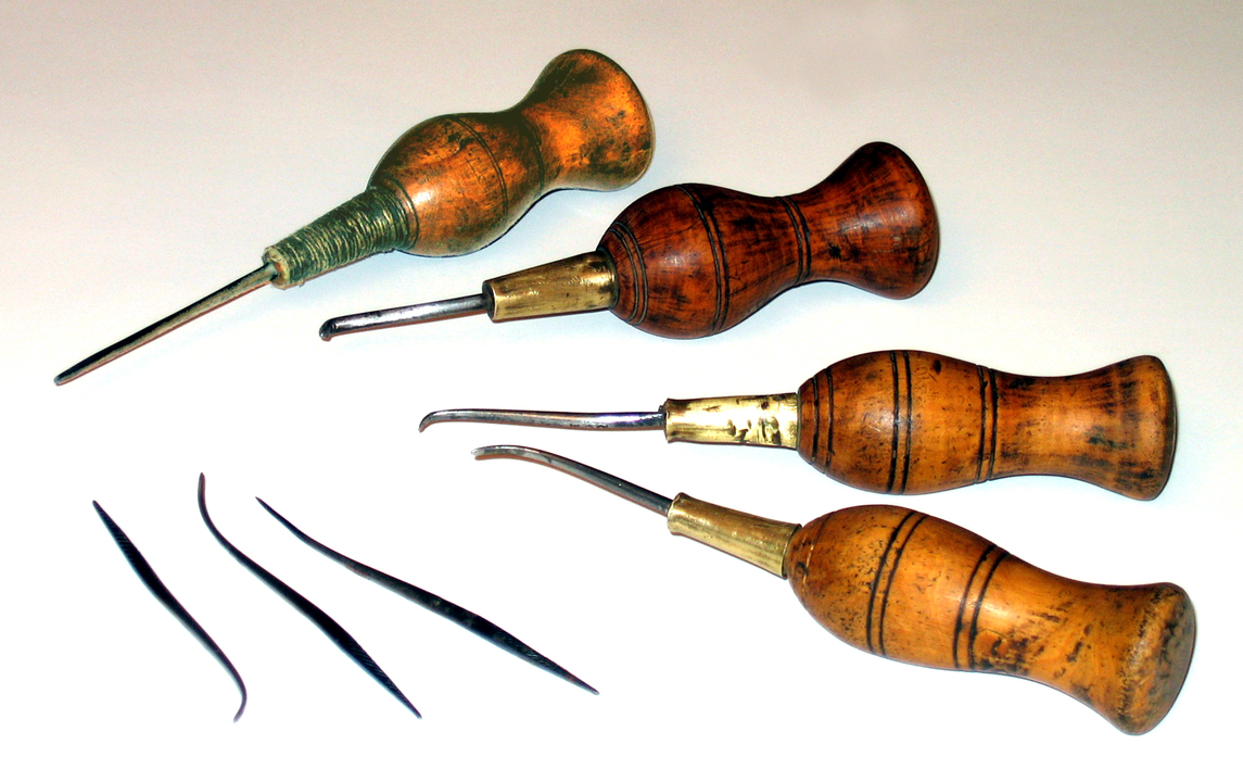 A collection of tools with wooden handles and sharp, pointed metal ends.