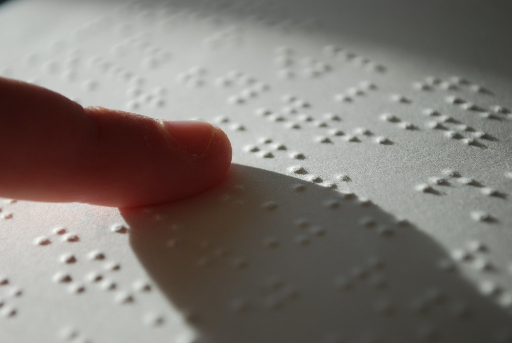 A finger feeling raised dots on a printed page of braille.