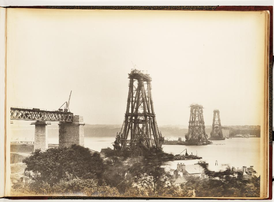 A sepia-toned photograph of a partially constructed bridge, with three cantilevers visible above the water.