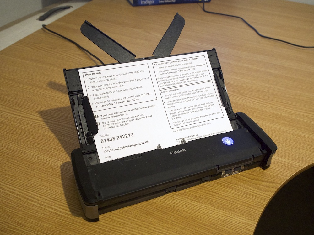 A black document-feed scanner sitting on a wooden desk.