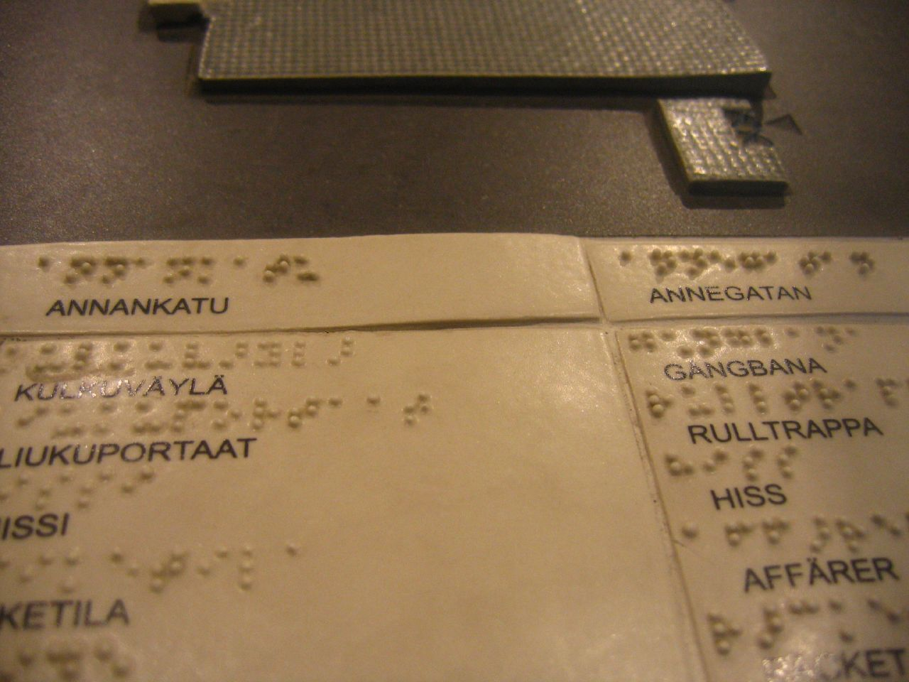 A page printed with Finnish words and embossed with braille.
