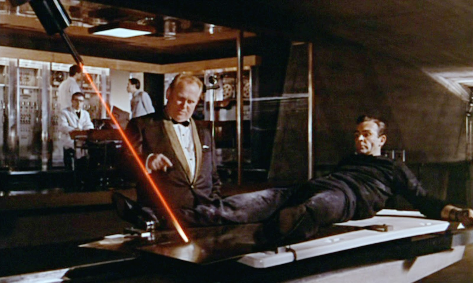 A man in all black (James Bond) is strapped to a table as another man in a golden suit (Goldfinger) overlooks. A large red laser is cutting through the table.