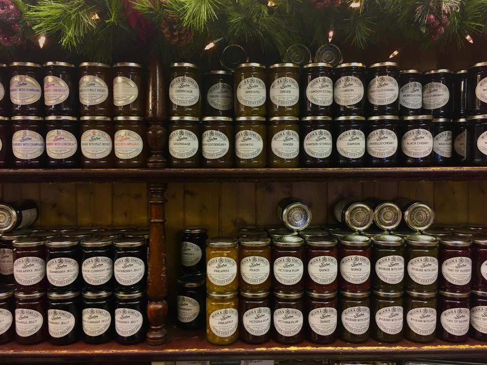 Two shelves, each stacked with two rows of jam in glass jars.