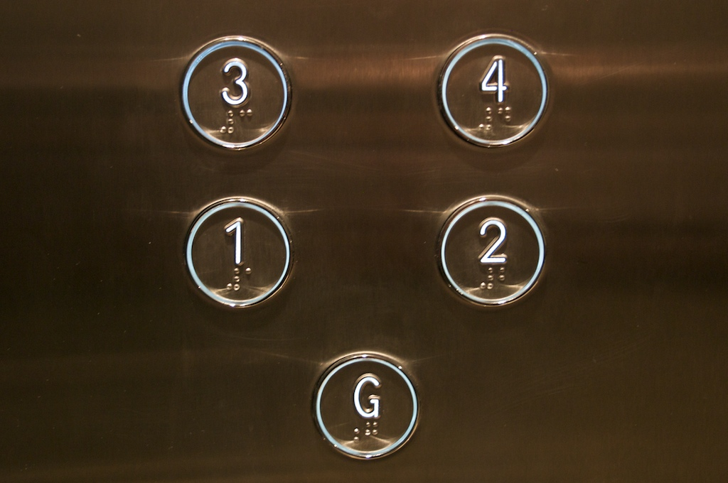 Buttons in a lift with printed numbers and braille inscriptions.