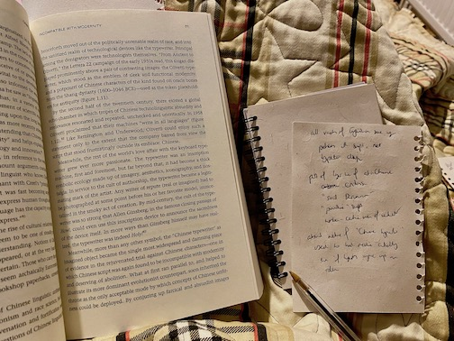 A book opened to a page halfway through (left) and some scraps of paper with scratchy handwriting (right).