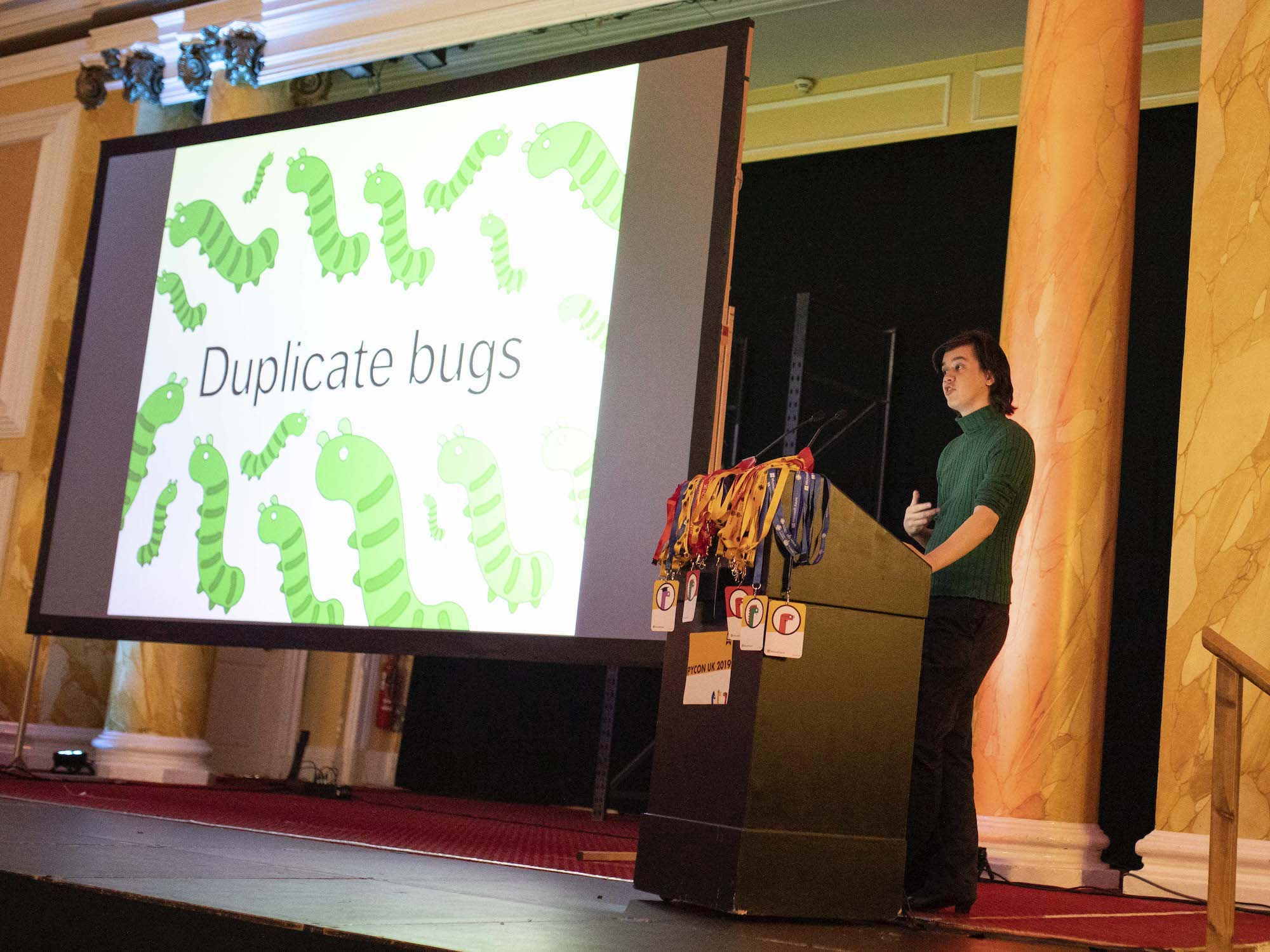 "A person in a green top standing at a podium, in front of a large screen with the words ""duplicate bugs""."