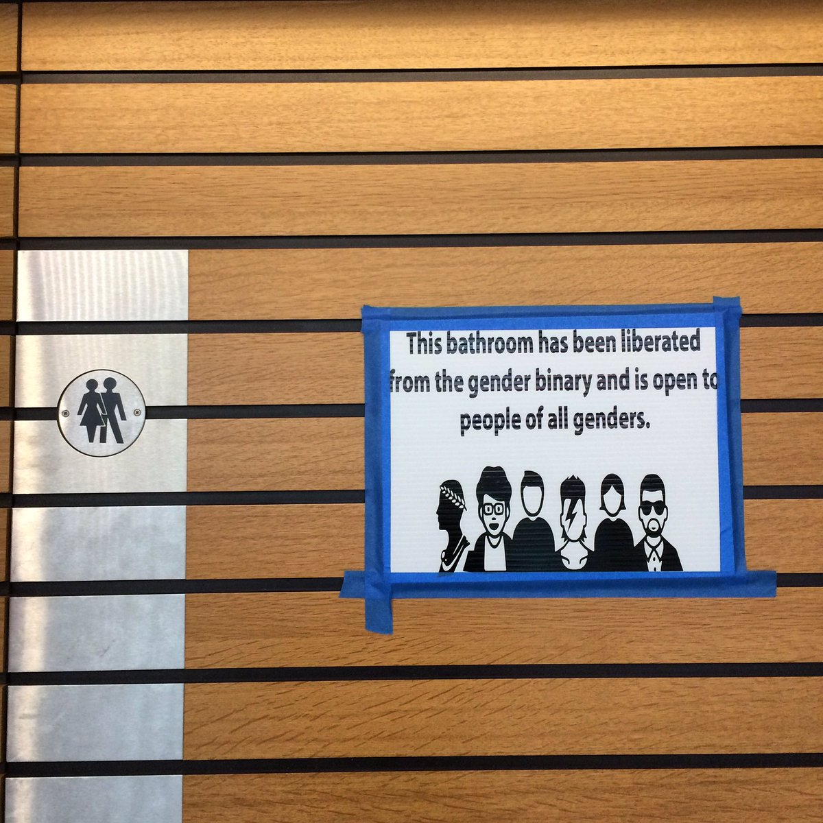 "A sign taped to a bathroom door saying ""This bathroom has been liberated from the gender binary and is open to people of all genders"", with an illustration of different people below the text."