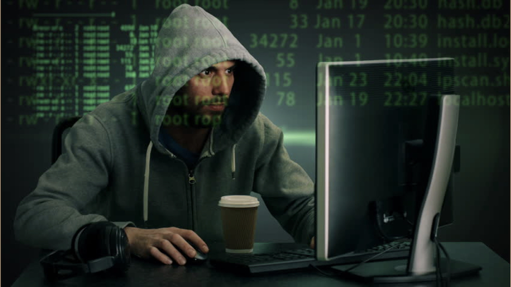 A photo of a man in a green hoodie, working at a computer with green text projected on their face.