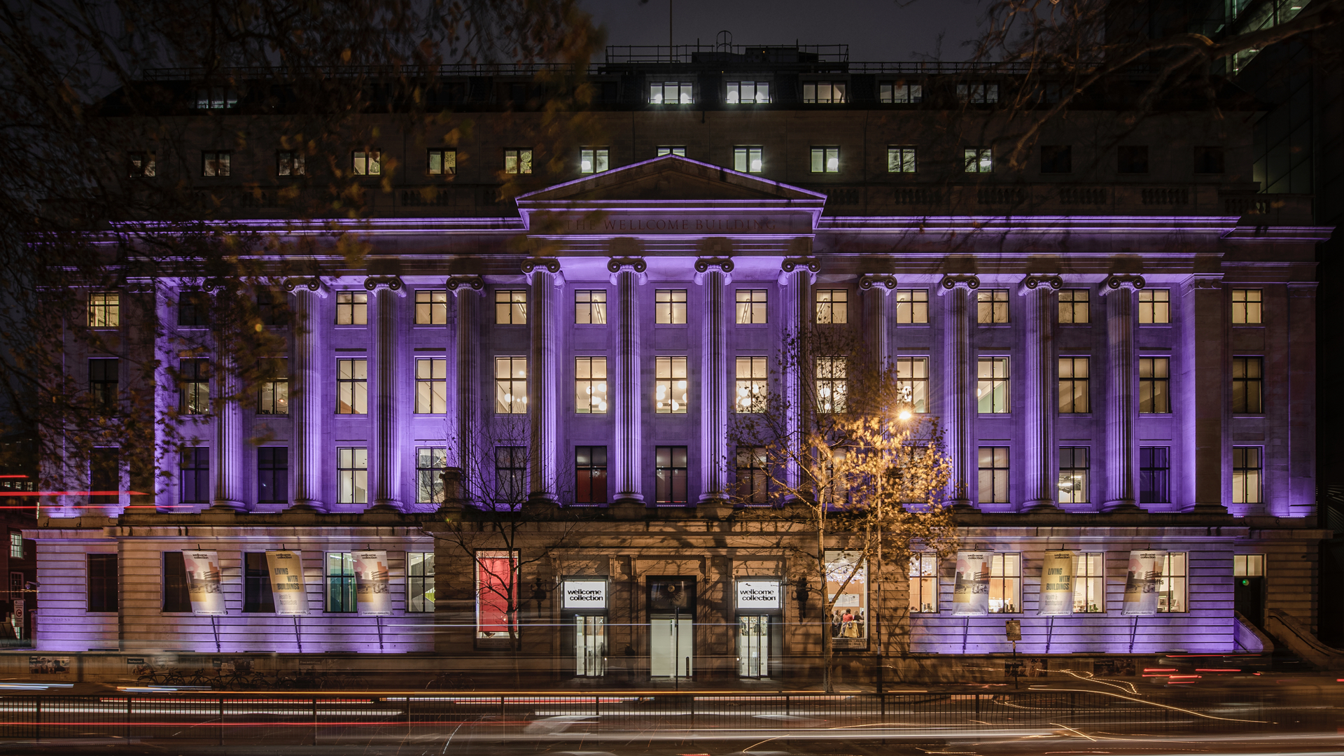The Wellcome Collection building, lit up in purple.