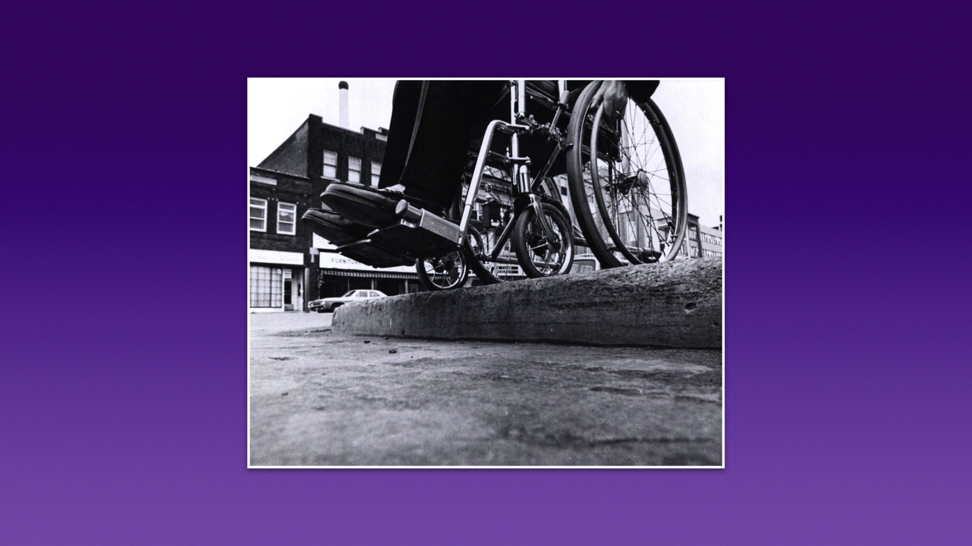 A black and white photo of a wheelchair standing at the edge of a raised curb.