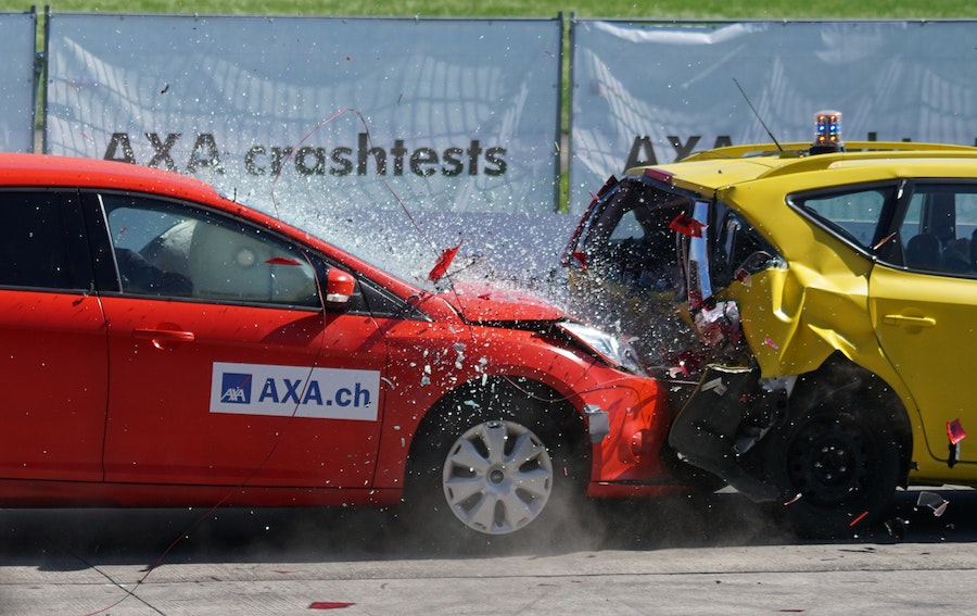 A red car (left) crashing into the back of a yellow car (right).