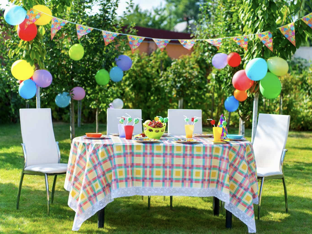 A photo of a table in a garden laid out for a party.